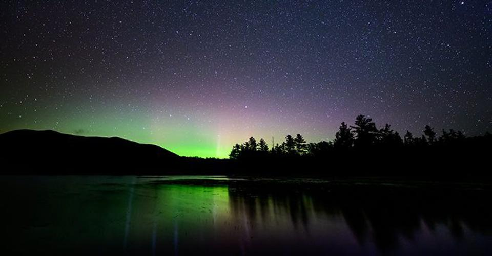 Stars sparkle above the brilliant colors of the aurora borealis as seen from the Appalachian Mountain Club's Maine Woods Initiative lands in central Maine.