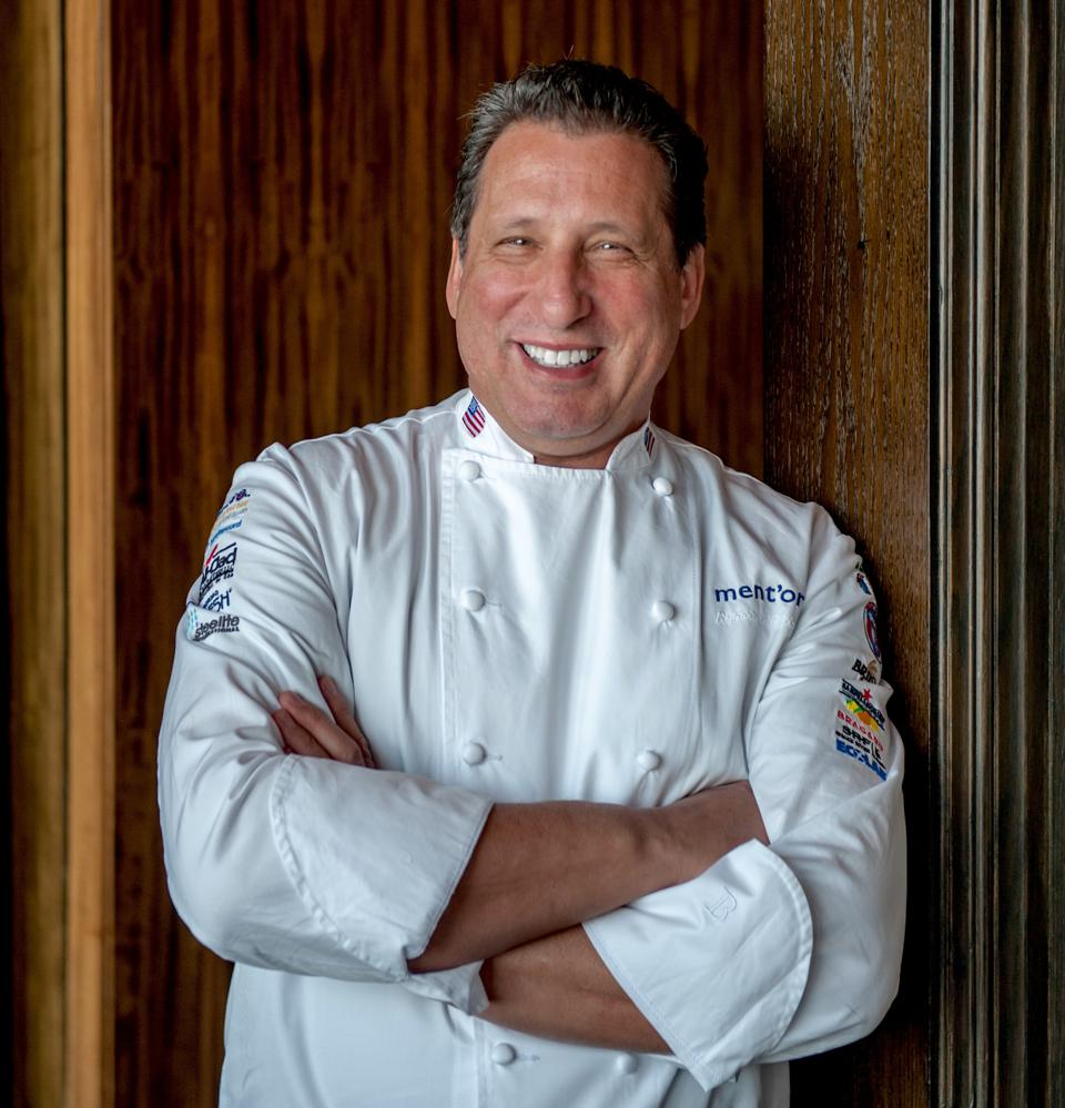 Chef Robert Sulatycky, smiling in his chef's whites with arms crossed