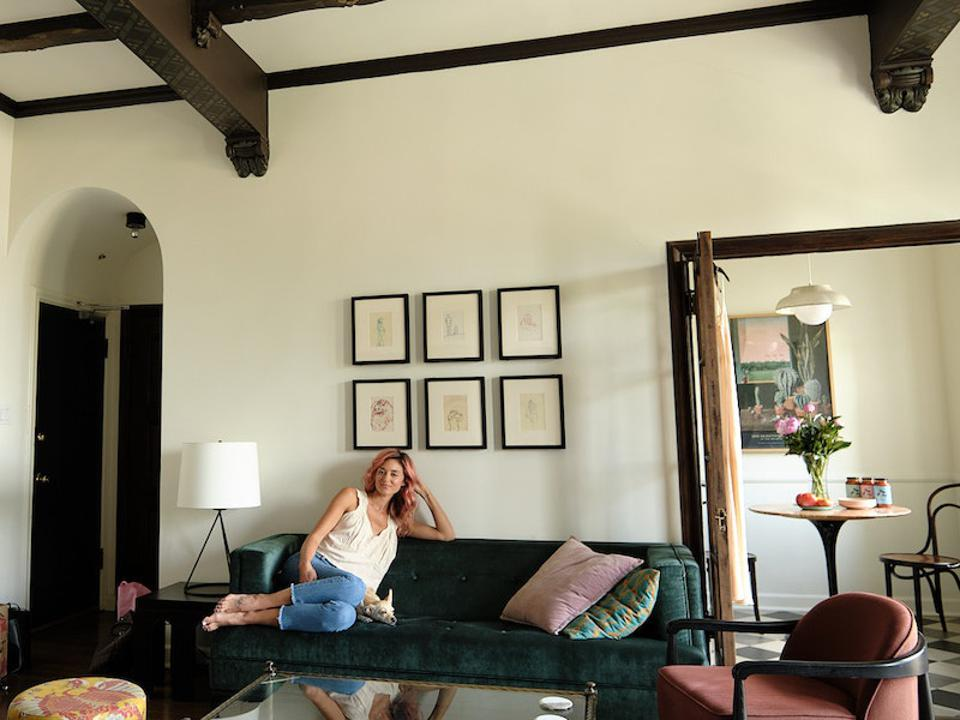 A woman with pink hair sits on a sofa in an art deco apartment
