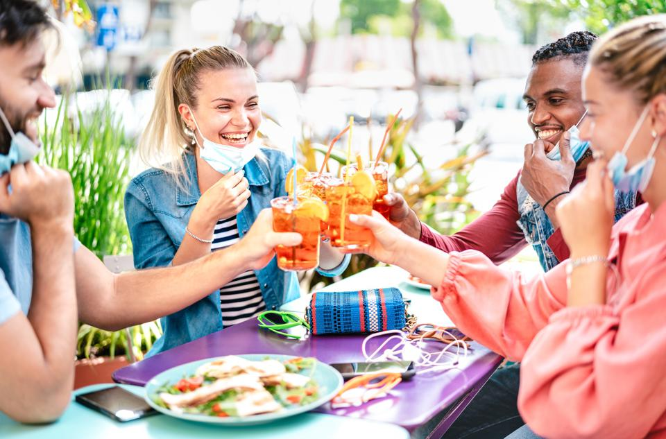 Friends drinking spritz at cocktail bar with face masks - New normal friendship concept with happy people having fun together toasting drinks at restaurant - Bright filter with focus on left woman