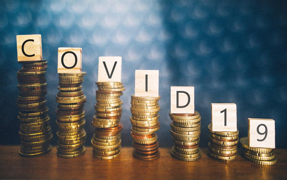 Coin stacks lined up in descending height order with 'Covid-19' spelled out on top.