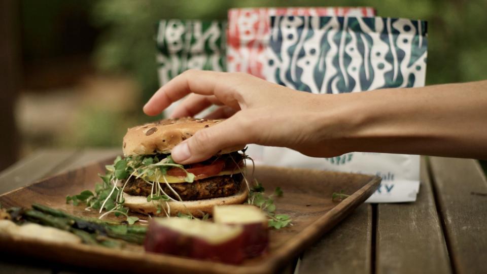 A hand reaches for an AKUA Kelp Burger.