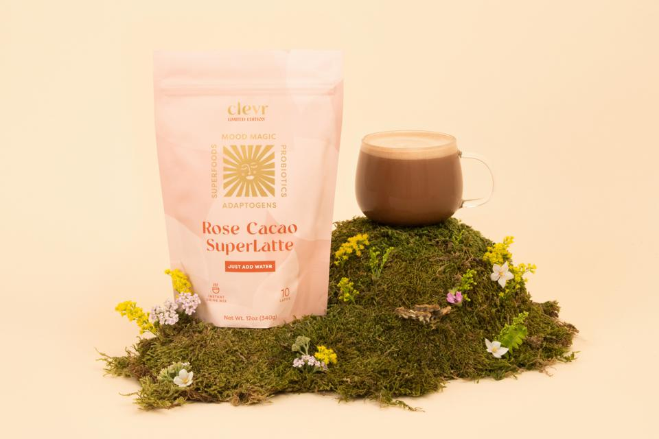 A cup of Clevr Rose Cacao Superlatte on a patch of grass.