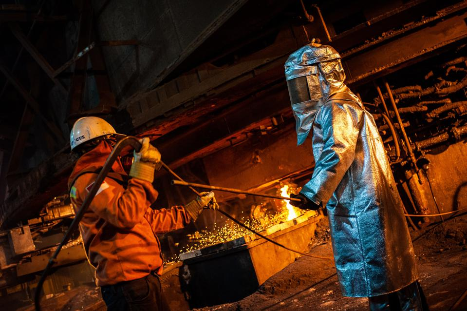 Workers seen supervising the flow of hot liquid metal as it...