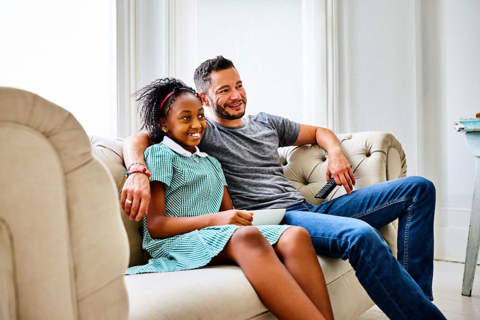 A trans man and his daughter watch TV