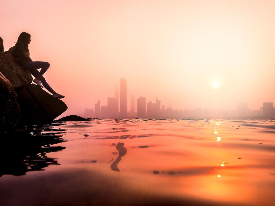 At sunset, a person sitting on a rock next to the water is in silhouette. The towers of Abu Dhabi City are in the distance.