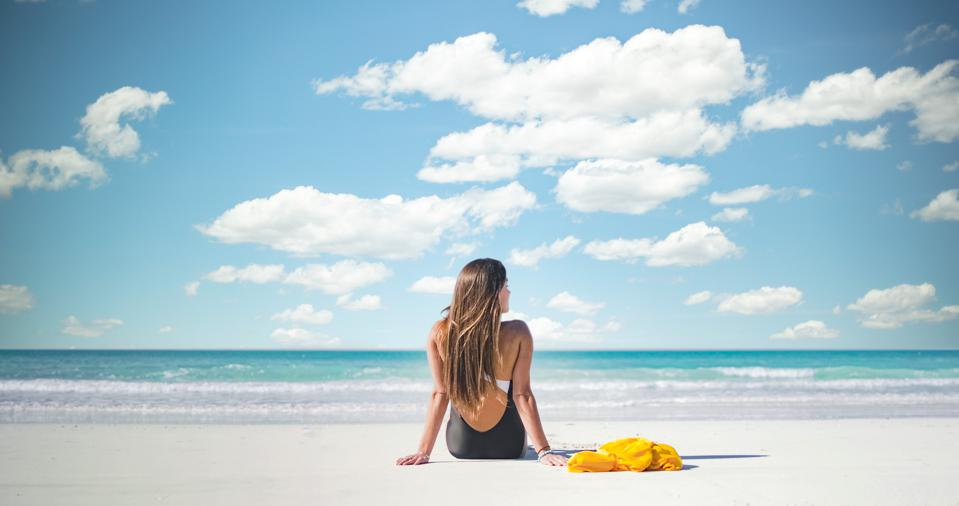 A woman with long hair wearing a black and white bathing suits sits on the white sand beach with her back to the camera. In the background is the blue-green sea and a blue sky with fluffy white clouds.
