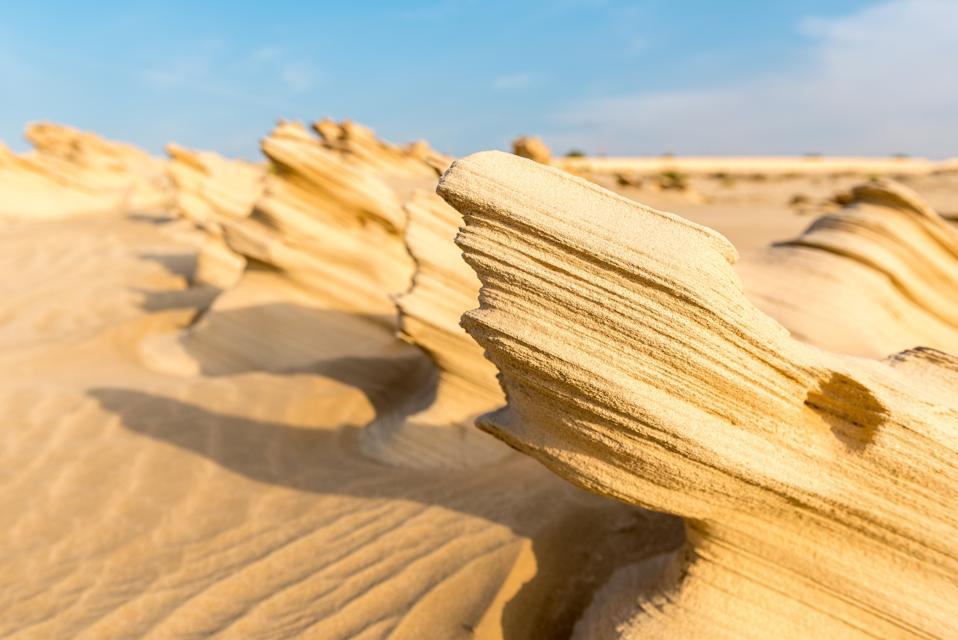 Natural windswept sand sculptures against a blue sky