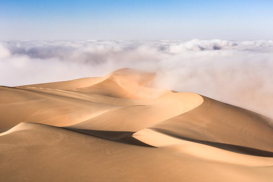Sweeping sand dunes with fog and clouds.