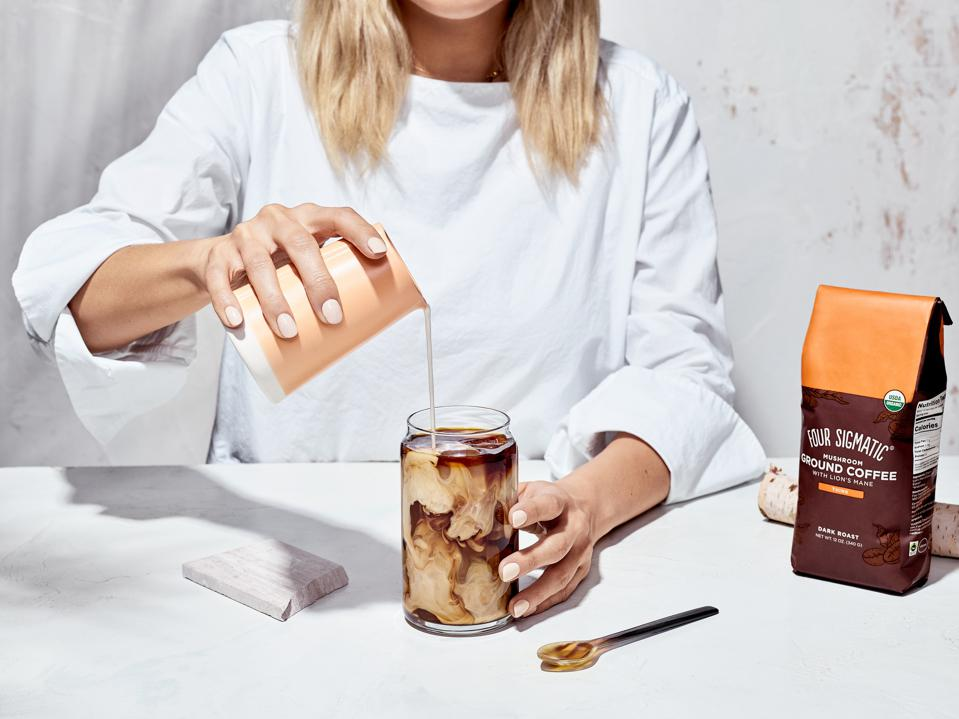 A woman pours milk into a cup of Four Sigmatic's Mushroom Ground Coffee.