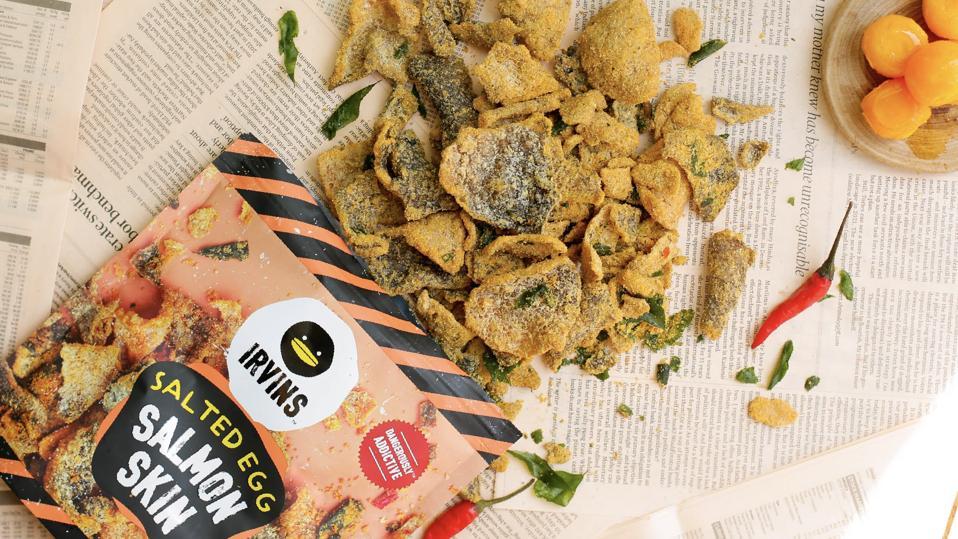 An open bag of Irvins' Salted Egg Salmon Skins on newspaper.