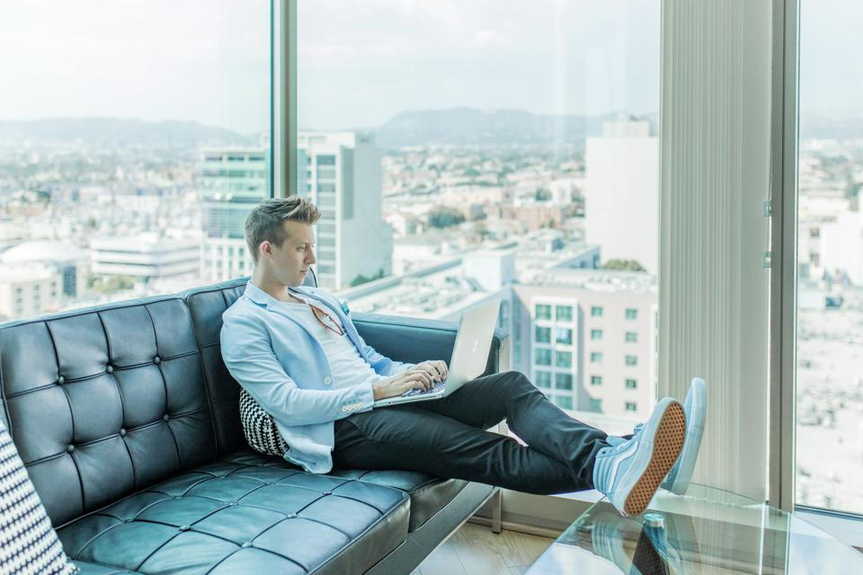 Man working on a laptop on a couch in a high rise apartment.