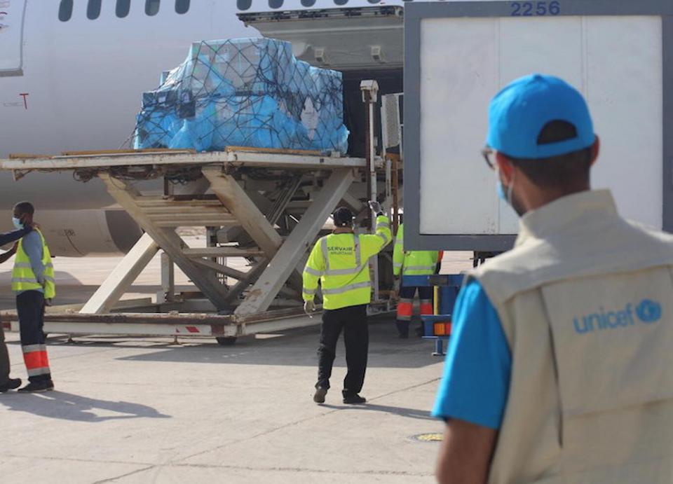 A UNICEF staff member supervises the unloading of a shipment of COVID-19 vaccine doses at Nouakchott International Airport in Mauritania as part of the global COVAX initiative.