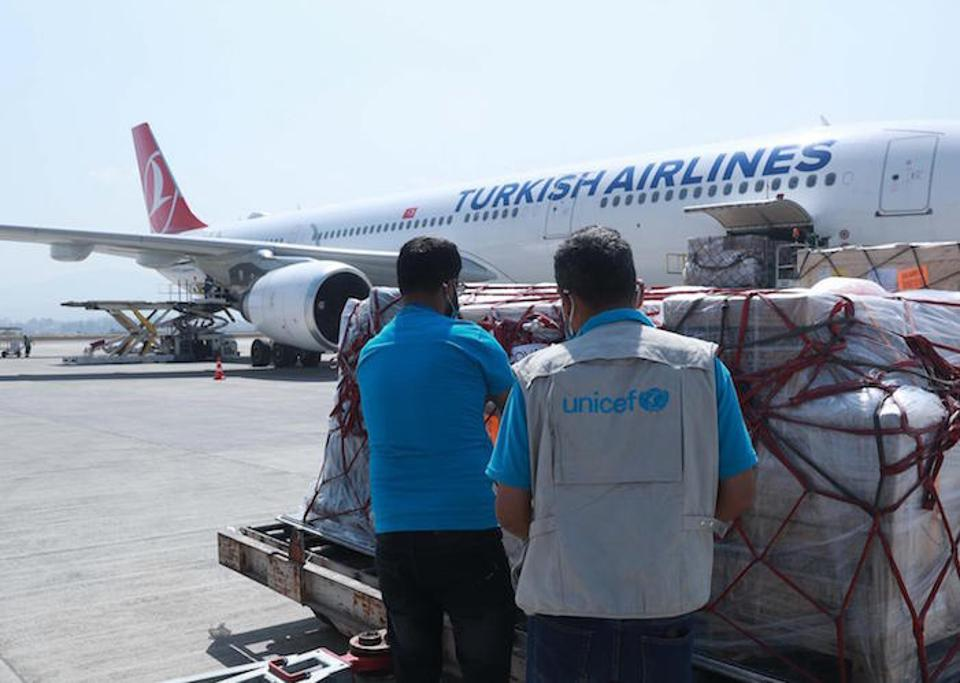 UNICEF staff oversee the delivery of Nepal's first consignment of syringes and vaccine safety boxes through the COVAX Facility at Tribhuvan International Airport in Kathmandu on March 11, 2021.