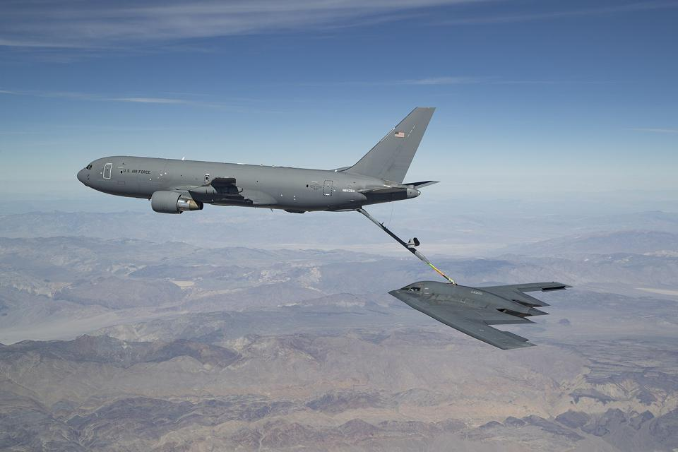 A KC-46 tanker being refueled in flight over California mountains.