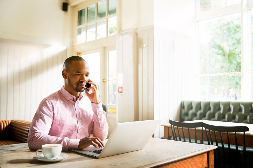 Man on smartphone using laptop