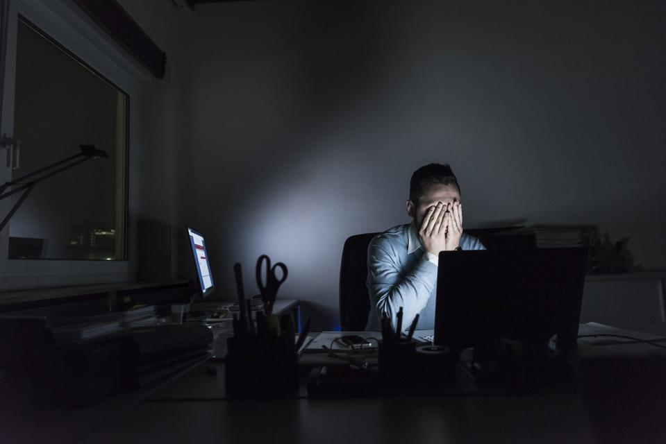 Exhausted businessman sitting at desk in office at night