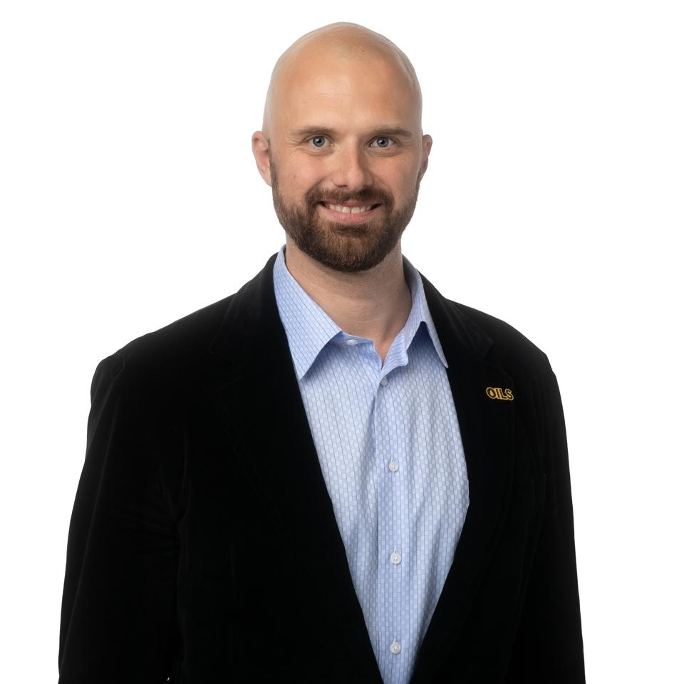 A bearded white man in a dark suit jacket smiles at the camera.