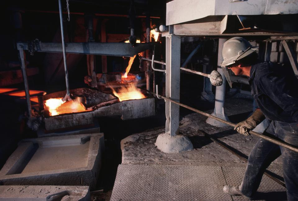 A foundry worker helps as molten iron is poured into moulds...