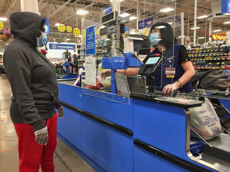 A cashier behind a plexiglass barrier working at a Walmart store during the Covid-19 pandemic.