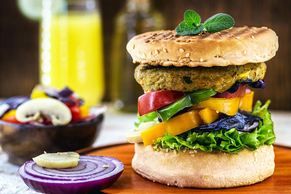 Vegan hamburger, Sandwich made without meat, with glass of green juice in the background. Sandwich with pepper, mushroom, tomato, lettuce and protein salad.