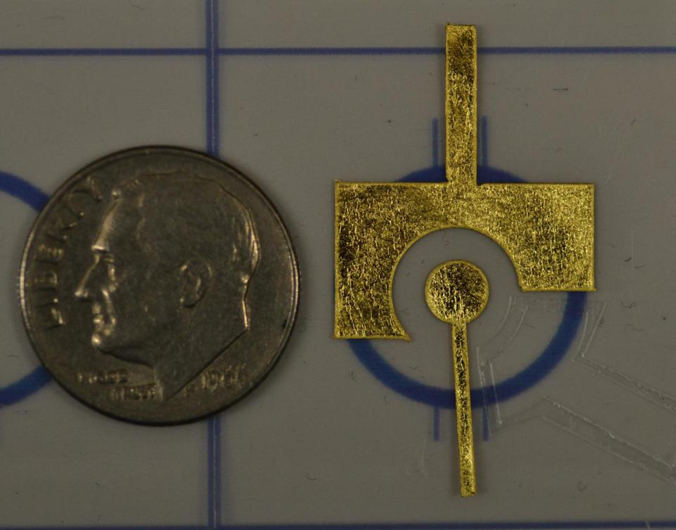 A dime next to two gold electrodes, which together are about the same size as the dime.