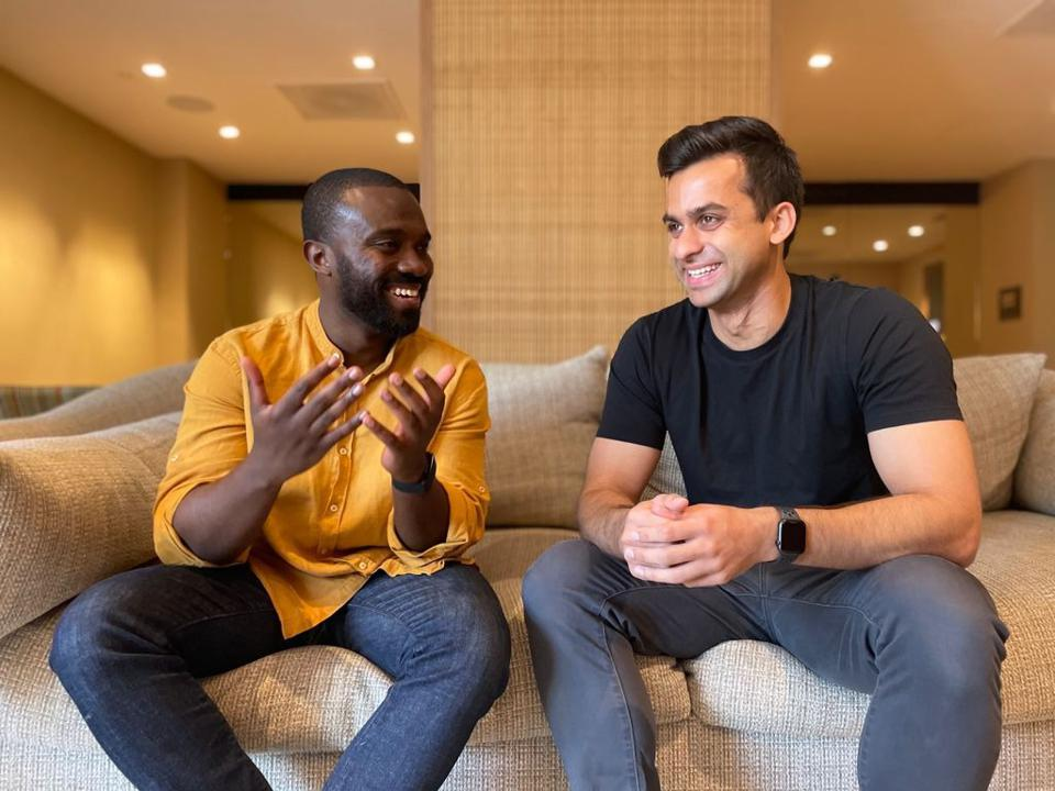 Two men sitting on a couch talking with one another.
