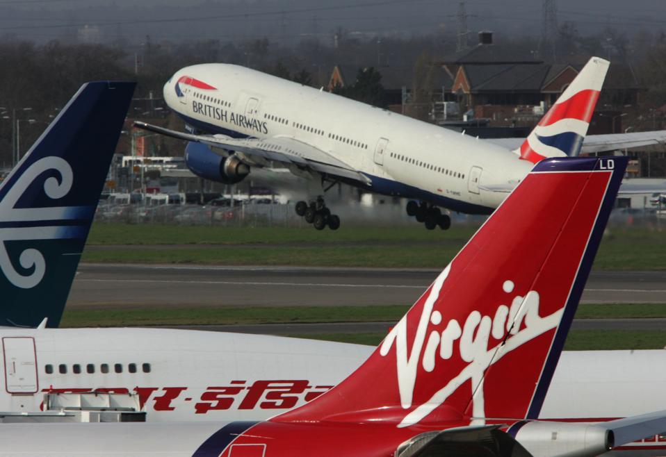 A BA 777 takes off behind a Virgin Airbus at Heathrow
