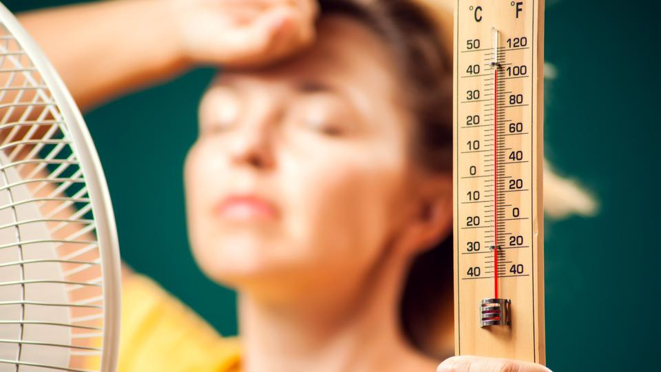 A portrait of woman in front of fan suffering from heat holding thermometer. Close up. Hot weather concept