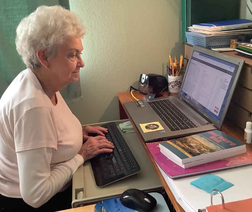 white haired mature lady typing on computer