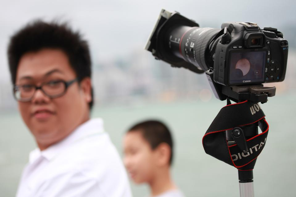 A man looks at a camera displaying a pic