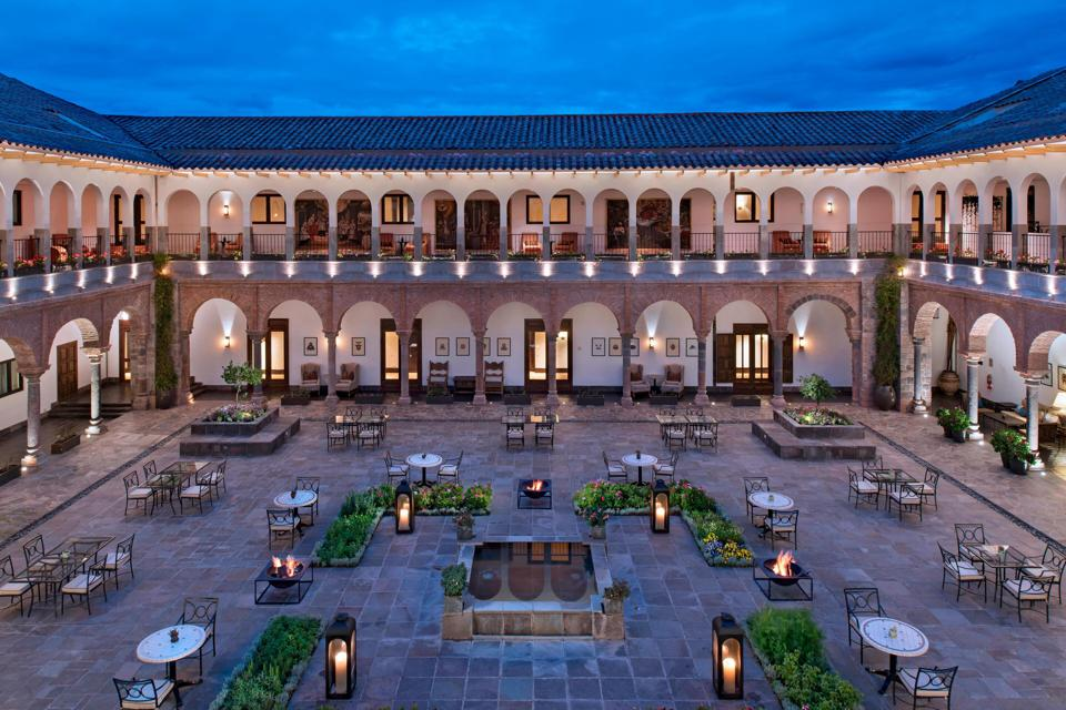 Three sides of a two-story building with arches along its outdoor hallways. The large interior courtyard has a stone floor, several tables and a few small gardens.