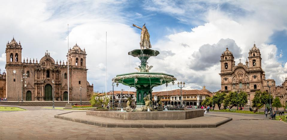A large fountain in the middle of a town square, with two colonial style buildings with towers in the background.