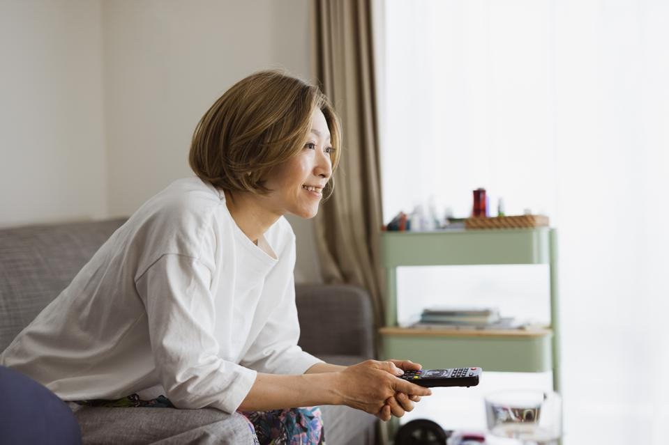 a woman watching tv on sofa
