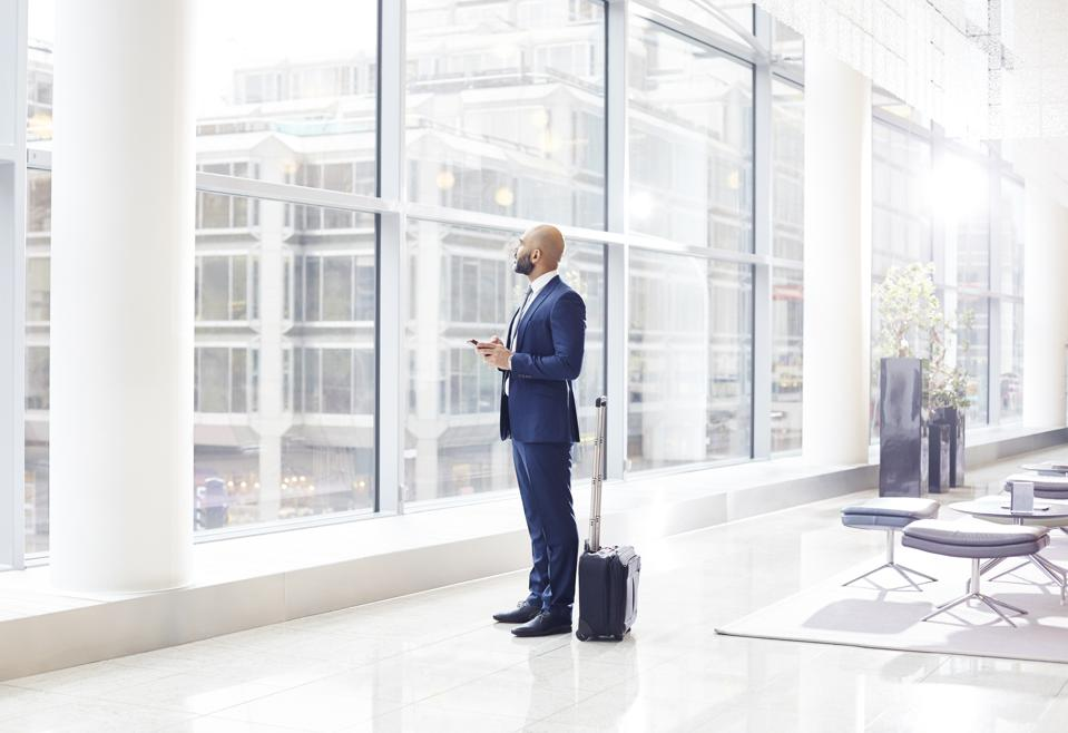 Businessman looking out a window at airport