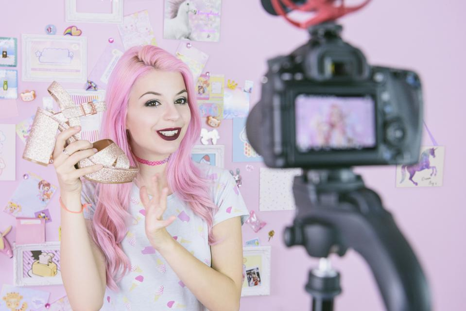 Female vlogger making social media video about fashion shoes for the internet
