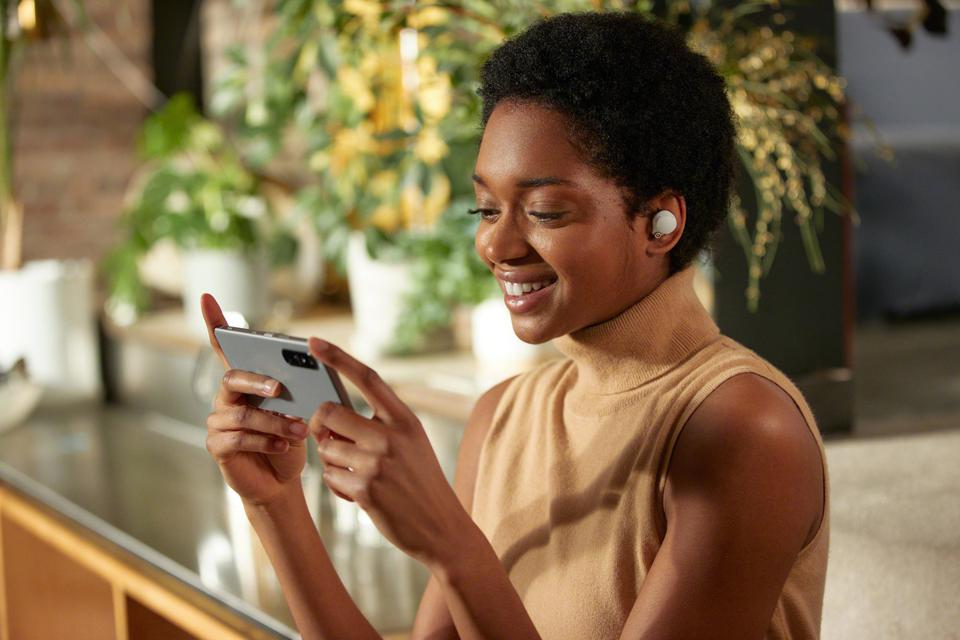 Woman playing on a phone while wearing white WF-1000XM4 earbuds