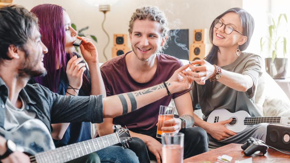 Young woman preparing to smoke joint with cannabis while relaxing with friends at home