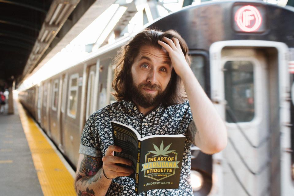 Author Andrew Ward looks perplexed as he holds his book The Art of Marijuana Etiquette on a New York City subway platform.