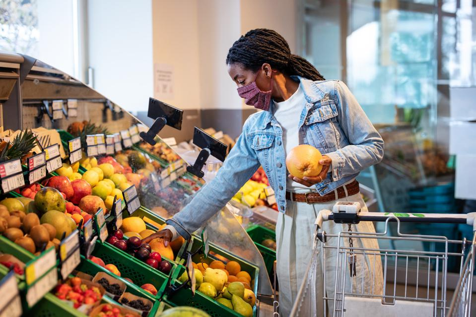 Female shops for fruit in grocery shop.