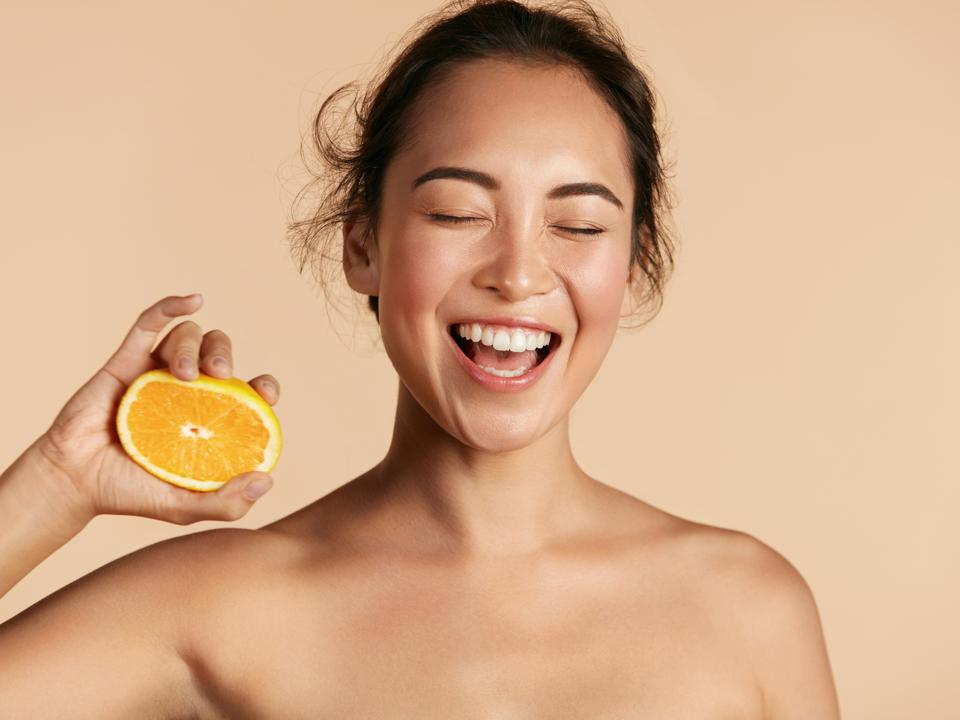 Smiling woman laughs while squeezing an orange.