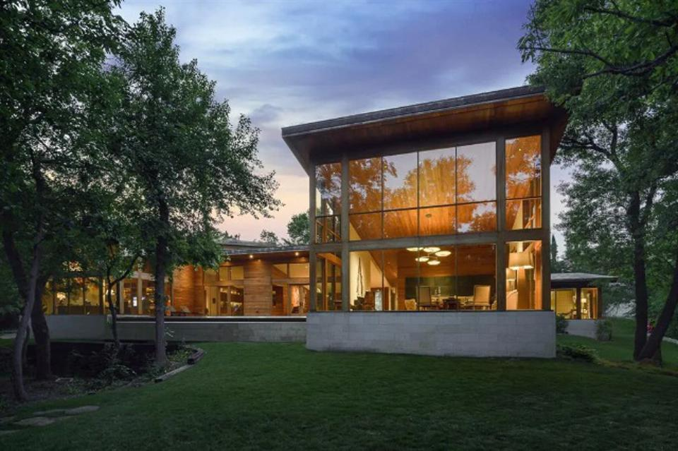 The 7196 square foot home features soaring glass windows.