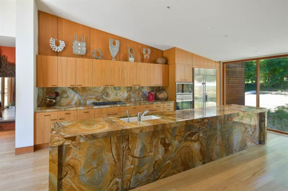 A 20 foot long kitchen island is made of colored quartzite.  The teak cabinets are topped with ceremonial South Sea necklaces.