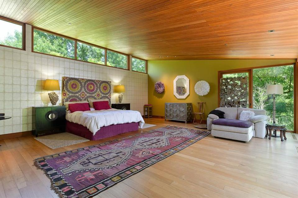 The tiled wall breaks through the teak wood in the master bedroom