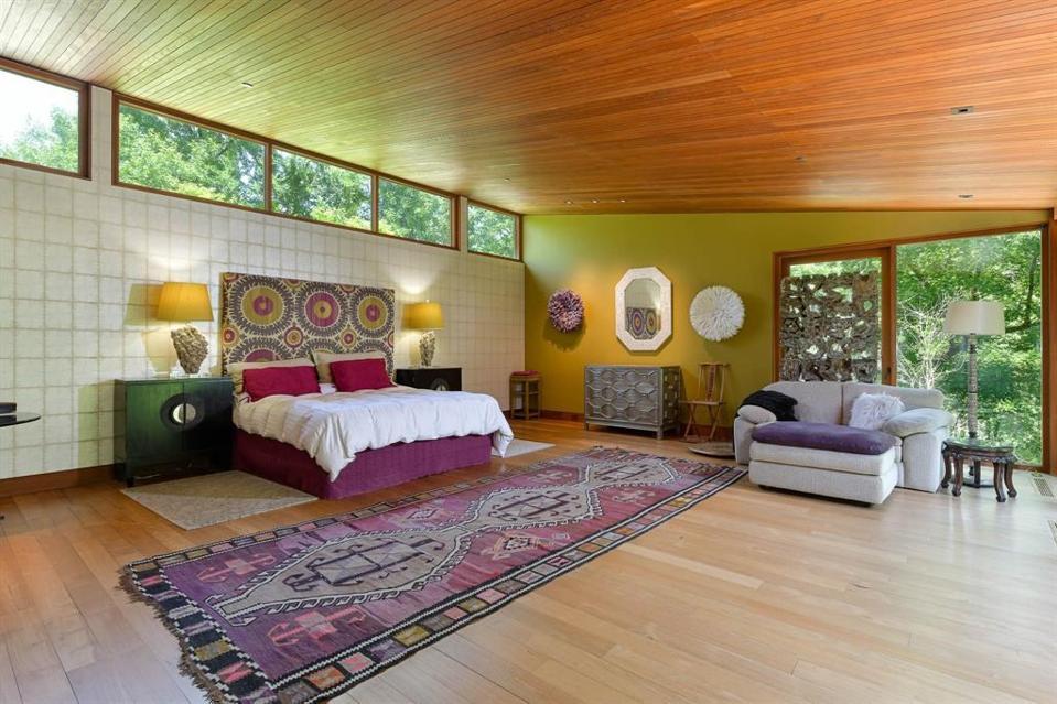 Tiled wall breaks the teak wood in the Main Bedroom