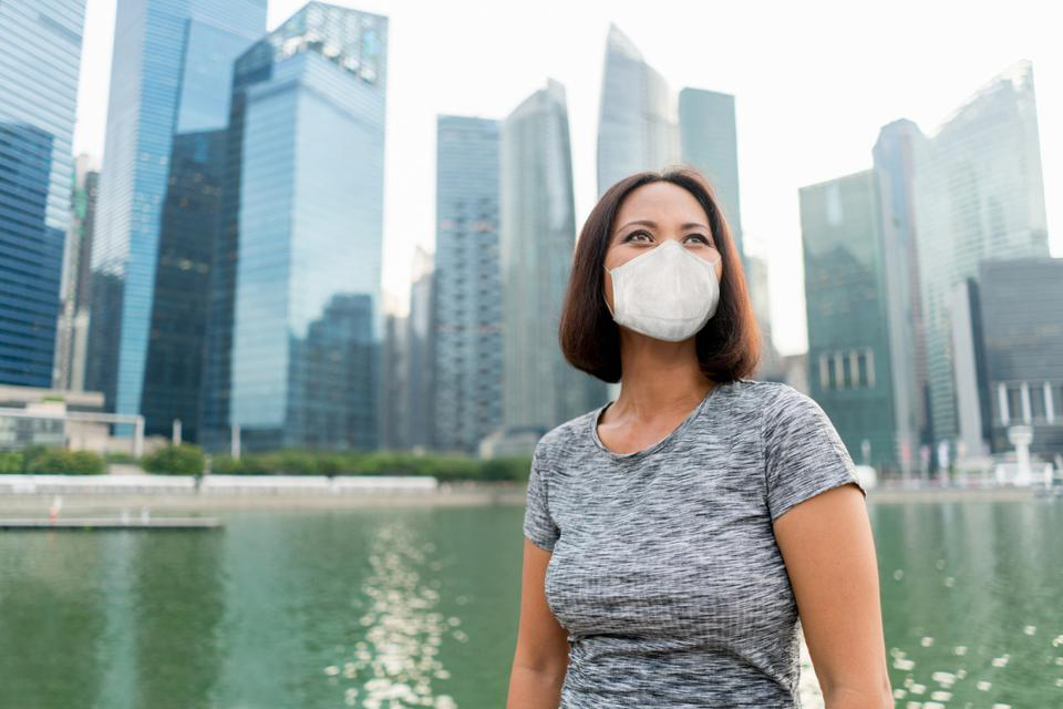 Business woman in Singapore wearing a facemask to avoid COVID-19