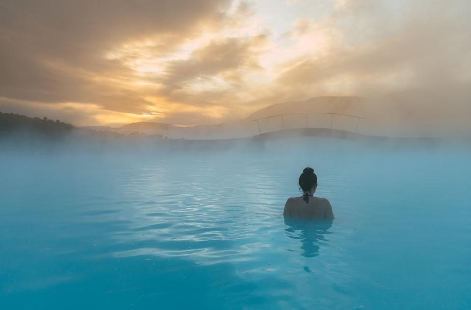 A woman relaxing in the ocean at dawn in Iceland.