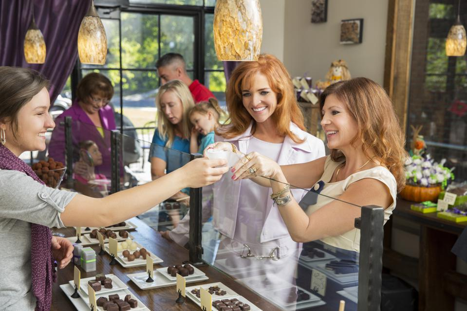 Happy female shoppers tasting chocolates in candy shop