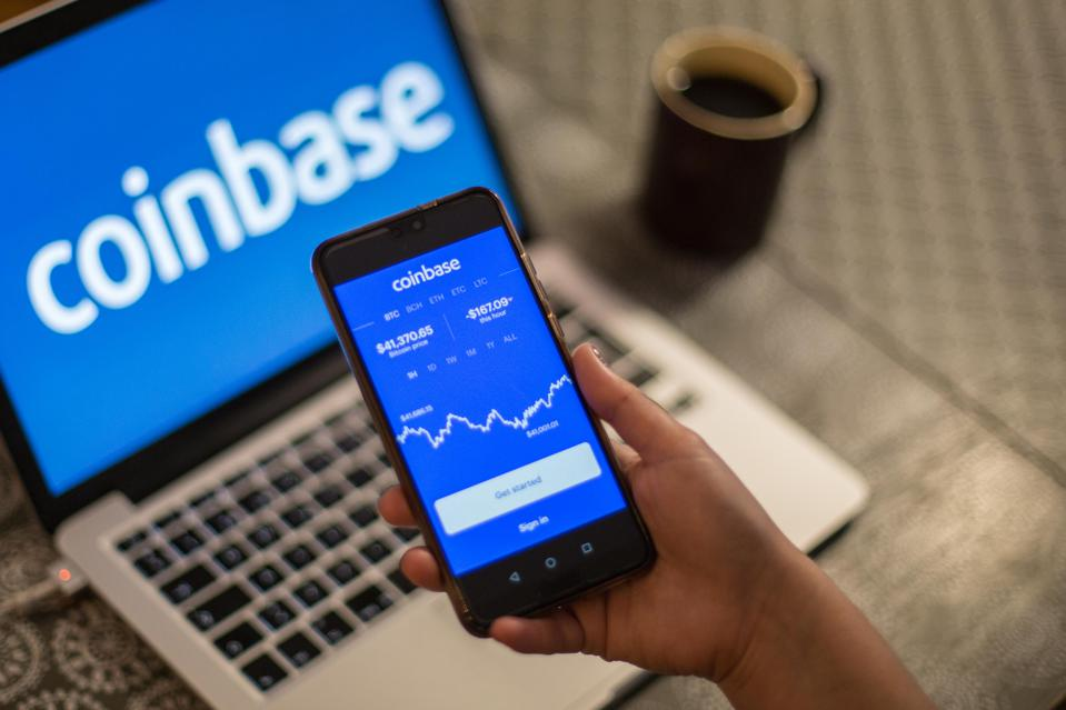 In this photo illustration a Coinbase App and logo is seen...