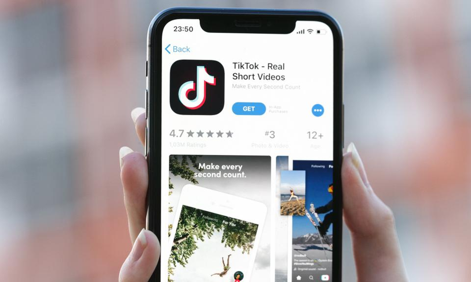 Screenshot of a hand holding an iPhone with the screen showing TikTok's App Store listing
